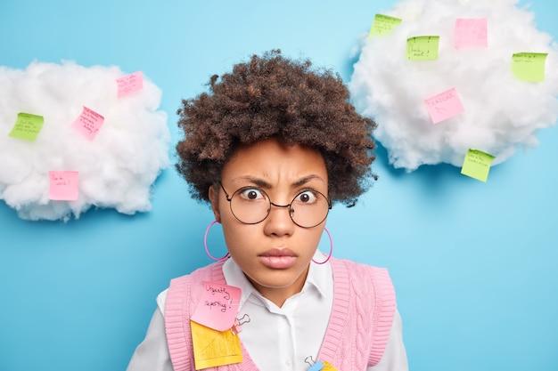 困惑したアフリカ系アメリカ人の学生のクローズアップショットは、カメラが丸い眼鏡をかけていることにショックを受けているように見えますステッカーにメモを作成します青い壁の上に隔離して行うさまざまなタスクがあります