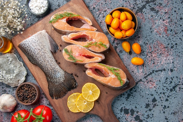 木製のまな板に生の魚レモンスライス緑コショウと青黒の色のテーブルに花のクローズアップショット