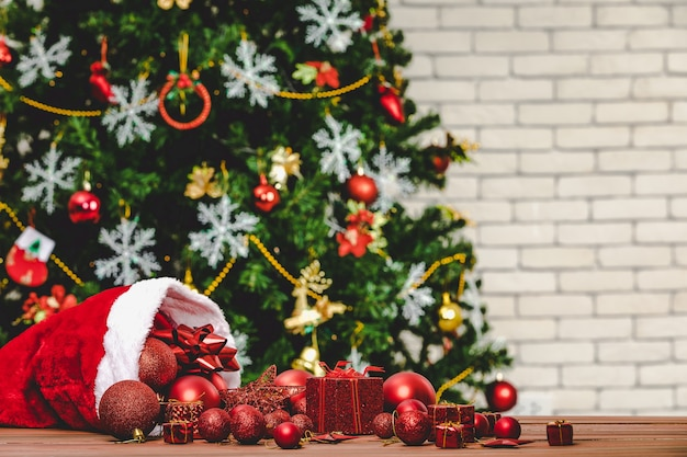 Крупным планом выстрел из красных декоративных элементов звездной сферы присутствуют подарочные коробки, льющиеся из рождественской шляпы на деревянный стол перед красивым полностью декором с сосной носки хлопьями льда в размытом фоне.