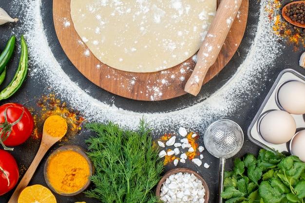 木の板の丸い生地と黒い表面の食品のセットの上に麺棒のショットをクローズアップ