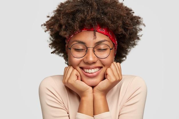 輝く笑顔で満足している浅黒い肌の女性のクローズアップショット、あごの下に手を保ち、喜びから目を閉じます、