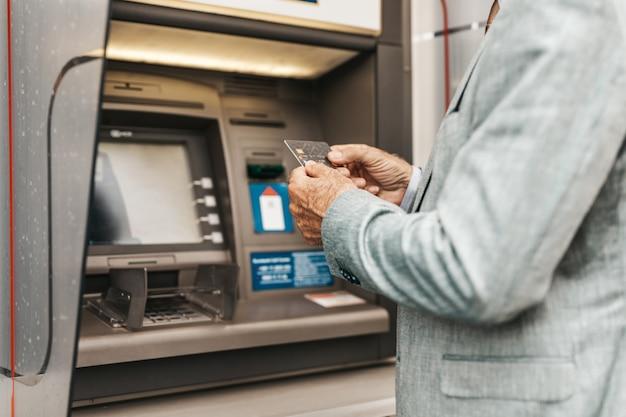 은행 신용 카드를 사용하여 수석 남자 손의 총을 닫습니다. 그는 atm 기계의 키패드에 핀 코드를 입력합니다.