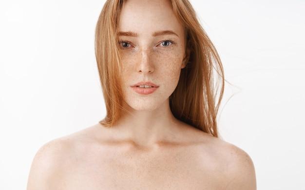 少し開いた口と夢のようなロマンチックな表情で裸で立っている官能的なフェミニンで魅力的な赤毛の女性のクローズアップショット。