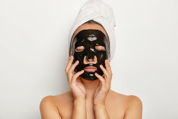 심각한 젊은 여자의 총을 닫습니다 검은 얼굴 마스크를 착용하고, 눈을 감고, 부드럽게 얼굴을 만지고, 머리에 감싸 인 수건을 착용합니다.