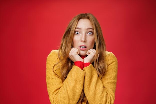 ショックを受けて怖がっている不安な赤毛の女性のクローズアップショット。黄色いコートを着て手を顎のラインに押し付け、口を開け、赤い背景に対する驚きと恐怖からカメラに向かって目を飛び出します。