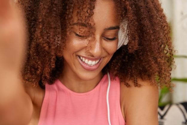 Снимок застенчивой женщины с густыми вьющимися волосами крупным планом