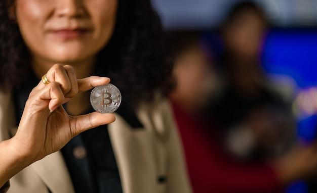 Крупным планом серебряный биткойн криптовалюта виртуальный токен монета в руке инвестора профессионального успешного женского предпринимателя-трейдера с копией пространства в размытом фоне.