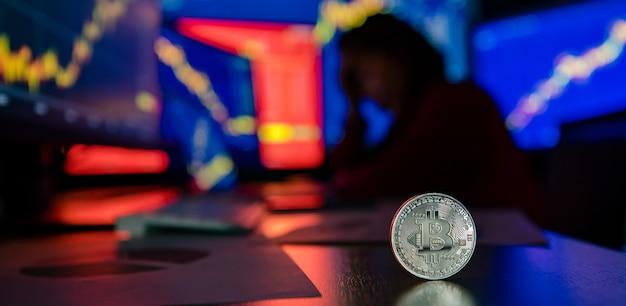不幸な失敗トレーダーと机の上の銀のビットコイン暗号通貨仮想トークンのクローズアップショット