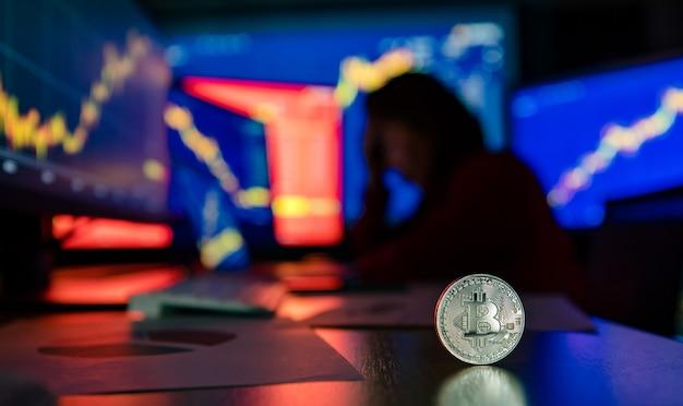 ぼやけた影の背景でコンピューターモニター画面のグラフチャート値の損失を見て動揺して不幸な失敗トレーダー投資家と机の上の銀のビットコイン暗号通貨仮想トークンのショットを閉じます。