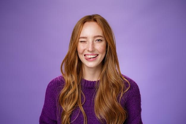 Крупным планом искренняя и счастливая смешная милая рыжая женщина с длинными рыжими волосами, счастливо подмигивающая и торчащая языком по-детски и беззаботно, весело позирует на фиолетовом фоне.