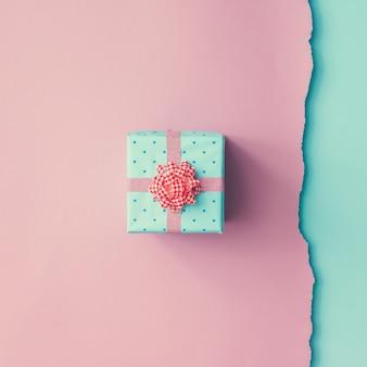 핑크 블루 벽에 핑크 리본으로 감싸 인 작은 선물의 총을 닫습니다. 최소한의 개념. 평평하다. 평면도.