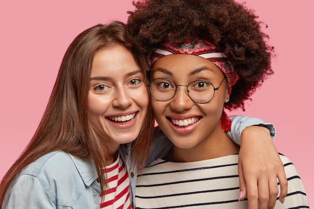 Крупным планом улыбающиеся разные лучшие подруги тепло обнимаются, радостно смотрят, широко улыбаются, показывают белые зубы