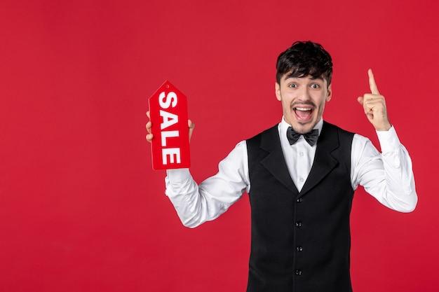 격리된 빨간색 배경을 가리키는 판매 아이콘을 보여주는 목에 나비가 달린 제복을 입은 흥분한 남자 웨이터의 미소를 클로즈업
