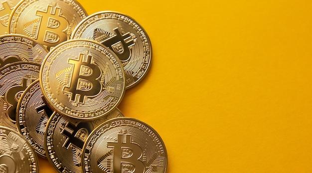 노란색 배경 및 복사 공간에 일부 bitcoins의 총을 닫습니다