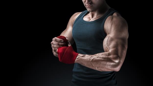 검은 배경에 손을 감싸는 강한 남자의 클로즈업 샷 남자는 검은 배경에 격리된 빨간색 권투 랩으로 손을 감싸고 있습니다