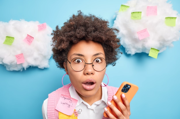놀란 아프리카 계 미국인 학생의 총을 닫습니다 뭔가가 입을 열어두고 휴대 전화를 사용하여 끈적 끈적한 다채로운 스티커로 흰 구름 주위에 정보 포즈를 확인합니다.