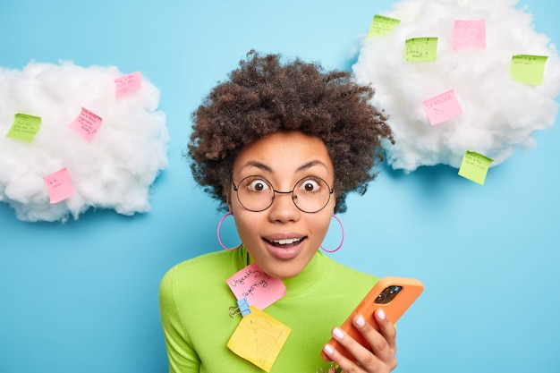 驚いた巻き毛の女性が意外と正面を見つめているクローズアップショットは、メモメモで囲まれた携帯電話のチェックメールボックスを保持し、屋内でより生産的なポーズをとろうとするリストを作成します。
