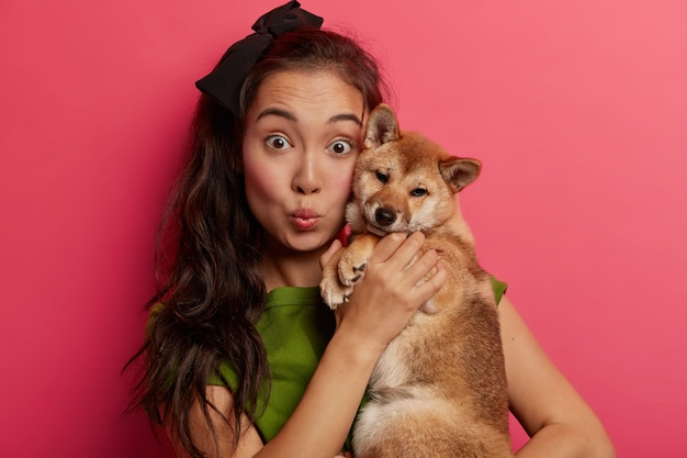 Крупным планом - удивленная темноволосая этническая женщина держит собаку сиба-ину возле лица, держит губы округлыми, чувствует близость с верным животным