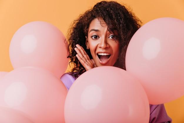 오렌지에 고립 놀된 화려한 아프리카 여자의 클로즈업 샷. 생일을 축하하는 곱슬 머리를 가진 멋진 흑인 소녀.