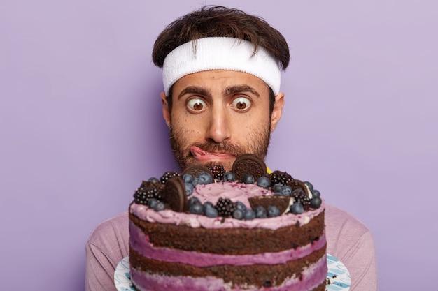 びっくりした男のクローズアップショットはおいしいケーキを見つめます