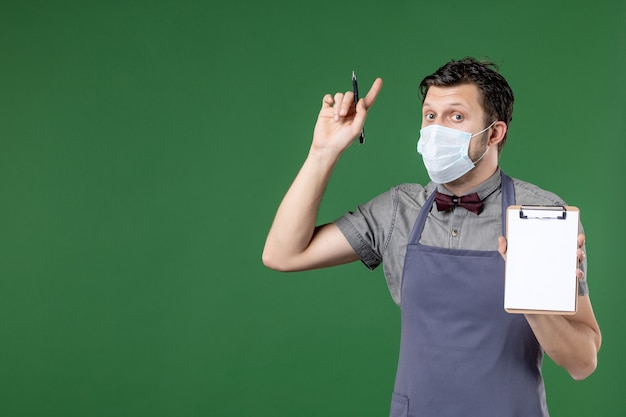 의료 마스크를 쓴 제복을 입은 놀란 남성 웨이터의 클로즈업 샷과 녹색 배경을 가리키는 주문서 펜을 들고