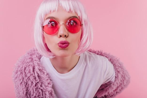 ピンクのインテリアでキスの表情でポーズをとってペルークで驚いた若い女性のクローズアップショット。写真撮影を楽しんでいるかつらのjocund白人の女の子