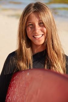 Снимок крупным планом талантливой молодой девушки-серфингистки, которая любит виндсерфинг, несет доску