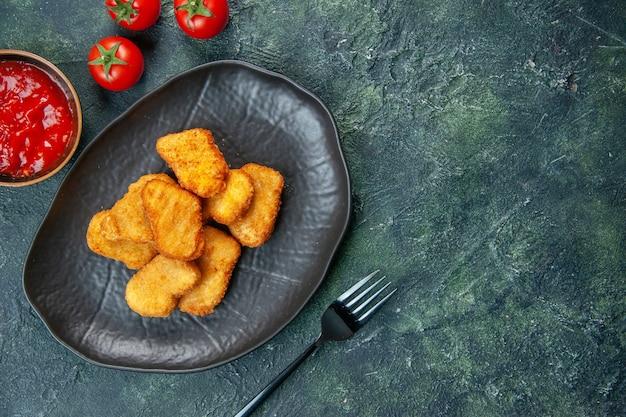 空きスペースのある暗い表面の右側にある黒いプレート トマト フォークのおいしいチキン ナゲットのクローズ アップ ショット