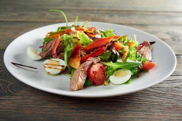 Закройте вверх по выстрелу вкусный свежий салат с жареным мясом и яйцами и соусом, зеленью, перцем, вкусным питанием, обедом, ужином, ужином, приготовлением ингредиентов рецепта.