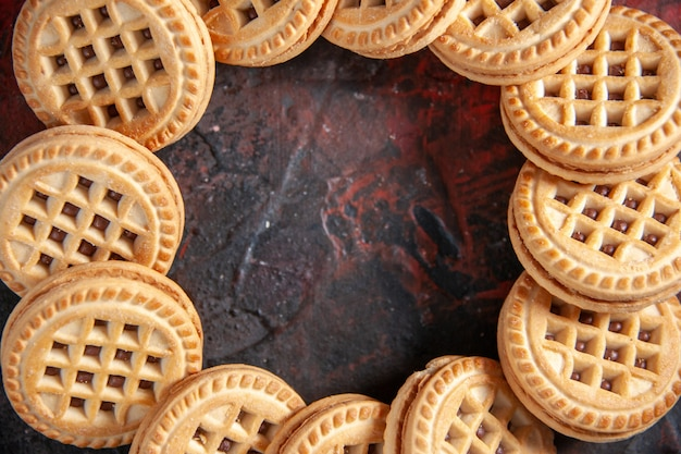 Крупным планом снимок вкусного сахарного печенья, расположенного в круглой форме на фоне смешанных цветов со свободным пространством