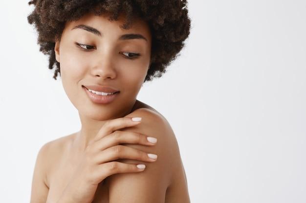 Снимок крупным планом нежной женственной афро-американской женщины с вьющимися волосами, поворачивающейся направо, касающейся плеча и улыбающейся с мягким мечтательным выражением лица