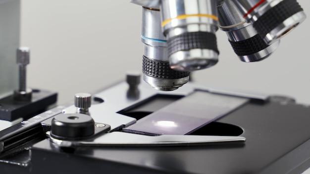 Крупным планом ученый изучает исследующий образец под микроскопом в лаборатории.