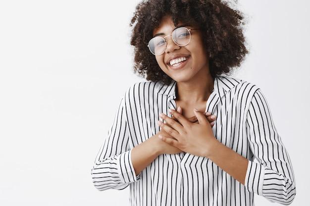 メガネのアフロの髪型と胸に手を繋いでいる笑顔とお世辞を受け取って喜んでいるストライプブラウスの感動と満足の幸せな浅黒い肌の女の子のクローズアップショット