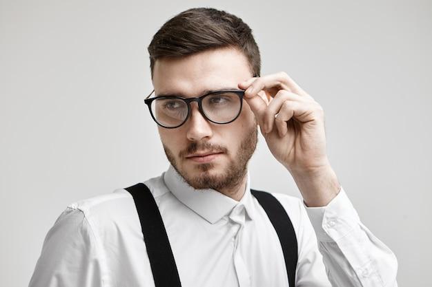 トリミングされた口ひげと無精ひげのポーズで白いスタジオの壁に隔離され、自信を持って顔の表情を持ち、彼のスタイリッシュな黒い眼鏡に触れて、流行に敏感な男のトレンディな外観のショットをクローズアップ