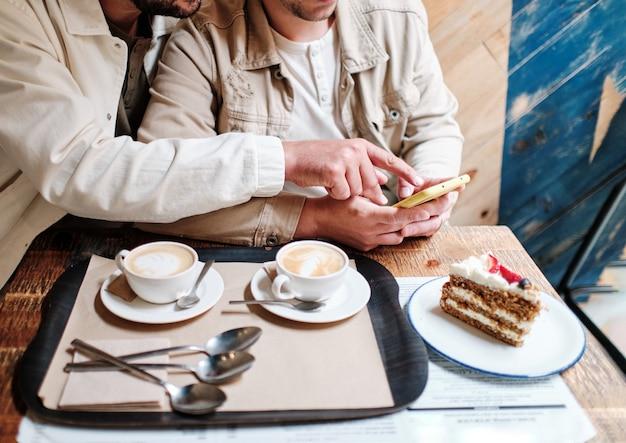 Крупным планом руки двух неузнаваемых мужчин-геев, использующих смартфон в кафе