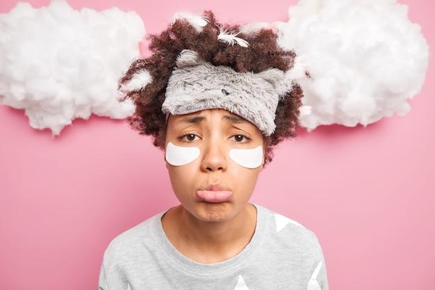 動揺した巻き毛の女性のクローズアップショットは不幸な表情の財布を欲求不満にしています下唇はピンクの壁に隔離されたパジャマとsleepmaskに身を包んだ目の下にパッチを適用します