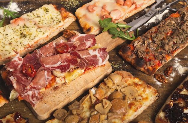 Закройте вверх по съемке разнообразия кусков домашней пиццы. прямоугольные порции. итальянская еда. ассортимент домашней пиццы.