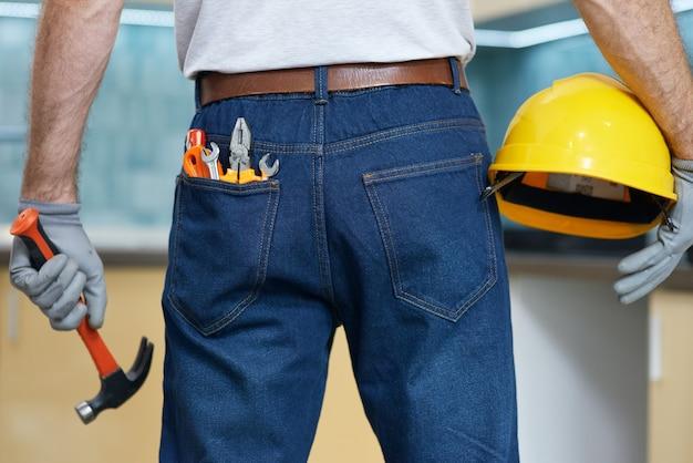 マンジーンズバックポケットプロの修理工のさまざまな配管ハンドツールのクローズアップショット