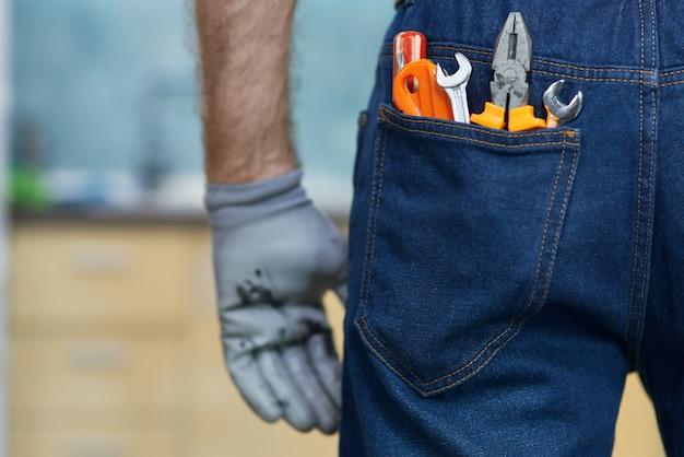 Крупным планом различные сантехнические ручные инструменты в заднем кармане джинсов ман