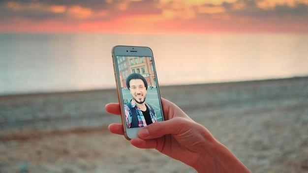 海岸でスマートフォンを使ったビデオ通話のクローズアップショット。若い男がチャット中です。