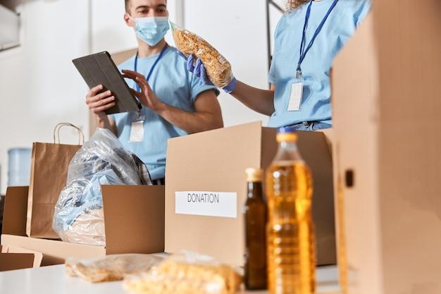 파란색 유니폼 보호 마스크와 장갑을 끼고 기부된 음식을 분류하는 자원 봉사자의 클로즈업 샷