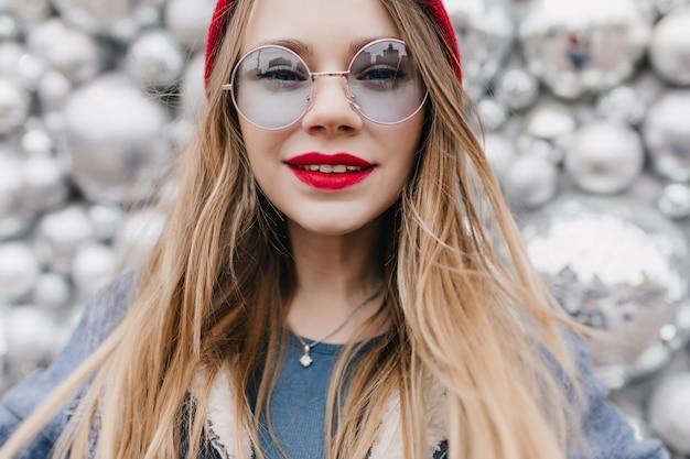 興味を表す眼鏡をかけた白い喜んでいる女の子のクローズアップショット。きらめく壁にポーズをとって赤い唇を持つ陽気な女性。