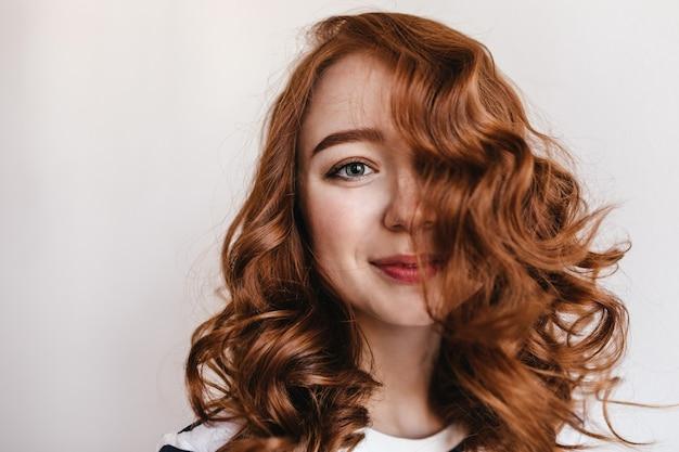 붉은 머리를 가진 매력적인 우아한 여자의 클로즈업 샷. 쾌활한 미소로 찾고 예쁜 생강 여성 모델.