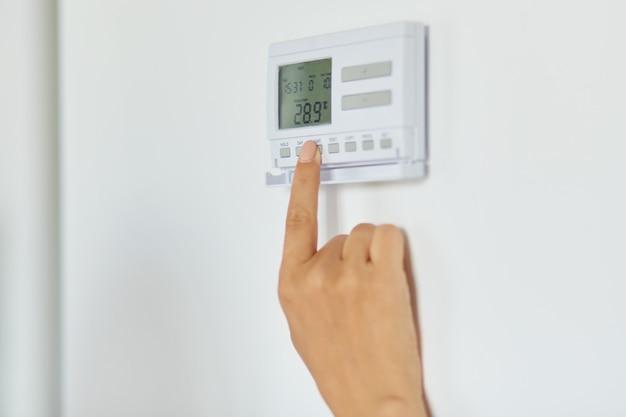 집의 흰 벽에 무선 온도 조절기로 난방 온도를 조절하는 여성 손, 알 수 없는 여성 누름 버튼, 스마트 홈을 클로즈업합니다.