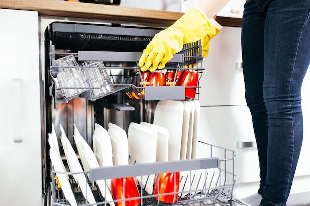 Крупным планом женская рука вынимать чистую посуду из посудомоечной машины.