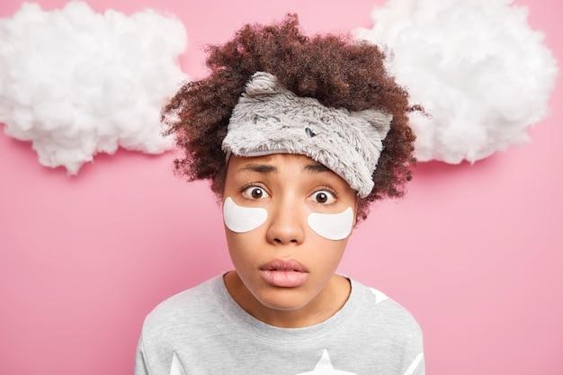 ピンクの壁に隔離されたパジャマに身を包んだしわを減らすために、スリープマスクが目の下にパッチを適用するカメラを着用している女性の驚くべき凝視のクローズアップショット