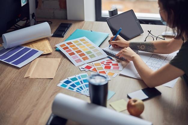 색상을 선택하는 노트북에서 메모를 하는 인테리어 디자이너의 작업 과정 클로즈업