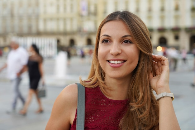 놀란 젊은 여성의 클로즈업 샷은 도시의 흐릿한 배경을 바라보고 있다