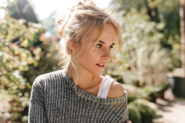 温室で灰色のセーターを着た、緑色の目を持つ若いブロンドの髪の女性のクローズアップショット