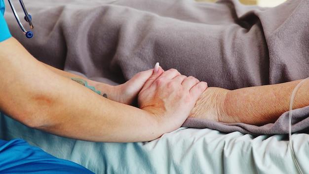병원 침대에 누워 있는 노부인의 손을 잡고 있는 백인 젊은 조수의 클로즈업 샷.